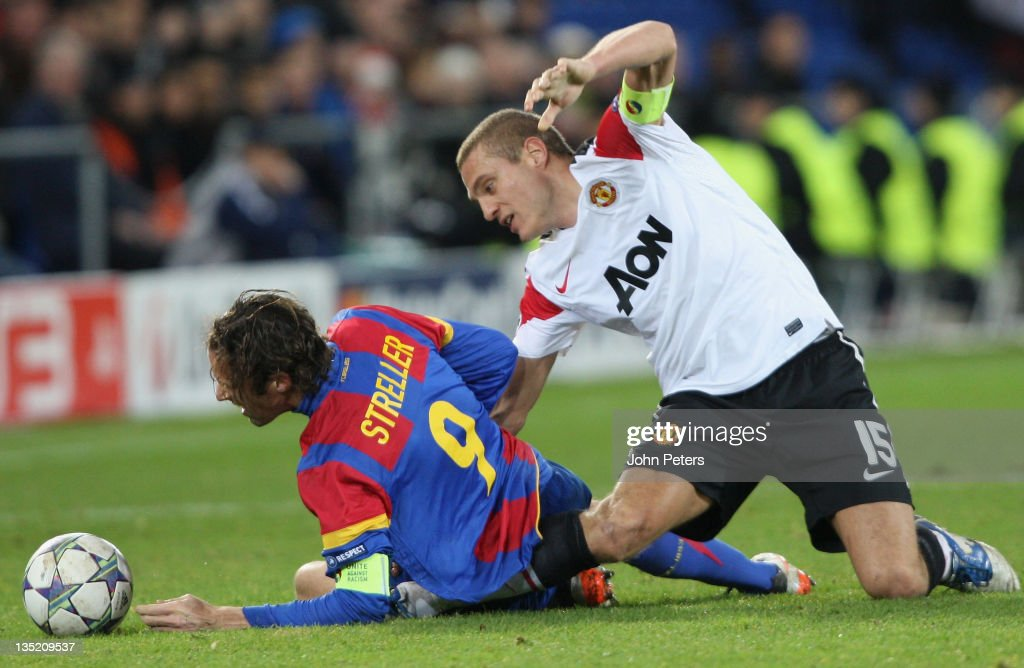 <a gi-track='captionPersonalityLinkClicked' href=/galleries/search?phrase=Nemanja+Vidic&family=editorial&specificpeople=497253 ng-click='$event.stopPropagation()'>Nemanja Vidic</a> of Manchester United picks up a knee injury while clashing with <a gi-track='captionPersonalityLinkClicked' href=/galleries/search?phrase=Marco+Streller&family=editorial&specificpeople=534494 ng-click='$event.stopPropagation()'>Marco Streller</a> of FC Basel during the UEFA Champions League Group C match between FC Basel and Manchester United at St Jakob-Park on December 7, 2011 in Basel, Switzerland.