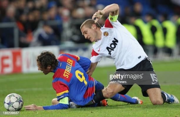 Nemanja Vidic of Manchester United picks up a knee injury while clashing with Marco Streller of FC Basel during the UEFA Champions League Group C...