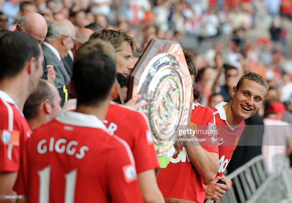 <a gi-track='captionPersonalityLinkClicked' href=/galleries/search?phrase=Nemanja+Vidic&family=editorial&specificpeople=497253 ng-click='$event.stopPropagation()'>Nemanja Vidic</a> of Manchester United smiles as team mate Edwin Van der Sar holds the trophy after the FA Community Shield sponsored by McDonalds between Chelsea and Manchester United at Wembley Stadium on August 8, 2010 in London, England.