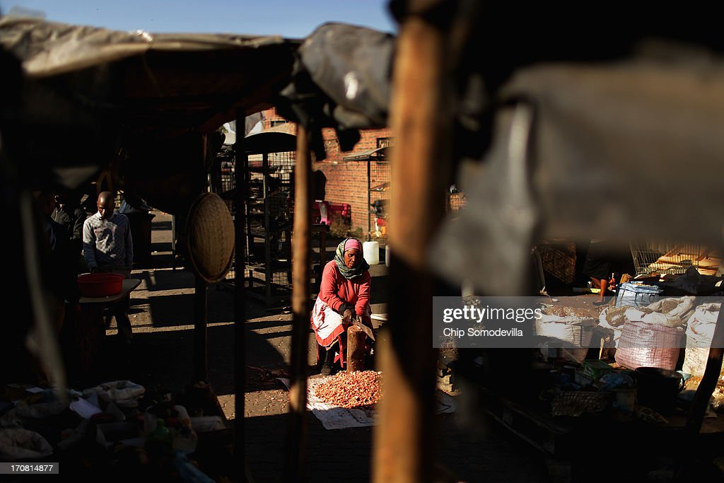 Nemko Dladla uses a machete to cut medicinal roots into bits that can be boiled into a broth at the Farady Market near downtown June 18, 2013 in Johannesburg, South Africa. Farady is one of the oldest markets in Johannesburg for 'muti,' or herbs, animal parts, good luck charms and healing potions used as medicines for traditional healing.