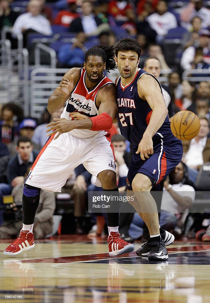 Nenê #42 of the Washington Wizards and <a gi-track='captionPersonalityLinkClicked' href=/galleries/search?phrase=Zaza+Pachulia&family=editorial&specificpeople=202939 ng-click='$event.stopPropagation()'>Zaza Pachulia</a> #27 of the Atlanta Hawks go after a loose ball at Verizon Center on December 18, 2012 in Washington, DC.
