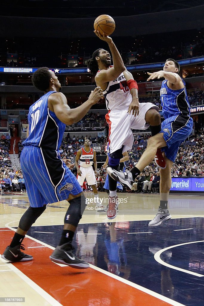 Nenê #42 of the Washington Wizards puts up a shot in front of Ish Smith #10 (L) and Nikola Vucevic #9 of the Orlando Magic during the second half at Verizon Center on December 28, 2012 in Washington, DC.