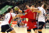 Nenad Vuckovic of Melsungen challenges for the ball with Johnny Jensen and Thomas Mogensen of Flensburg during the Bundesliga match between SG...