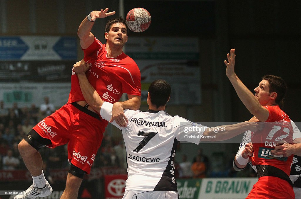 Nenad Vuckovic of Melsungen (L) passes the ball over Milutin Dragicevic of Kiel (C) during the Toyota Handball Bundesliga match between MT Melsungen and THW Kiel at the Rotehnbach Hall on September 28, 2010 in Kassel, Germany.