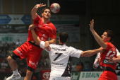 Nenad Vuckovic of Melsungen passes the ball over Milutin Dragicevic of Kiel during the Toyota Handball Bundesliga match between MT Melsungen and THW...