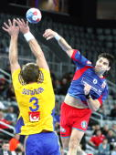 Nenad Vuckovic of Serbia scores a goal against Mattias Gustafsson of Sweden during the Men's World Handball Championships placement match of place...