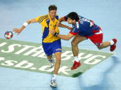 Nenad Vuckovic of Serbia tackles Jonas Larholm of Sweden during the Men's World Handball Championships placement match of place seven between Sweden...
