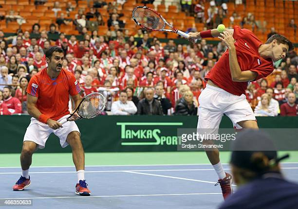 Nenad Zimonjic and Filip Krajinovic of Serbia in action against Marco Chiudinelli and Michael Lammer of Switzerland during their men's doubles match...