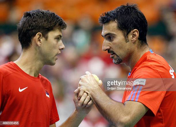 Nenad Zimonjic and Filip Krajinovic of Serbia talk during the match against Marco Chiudinelli and Michael Lammer of Switzerland during their men's...