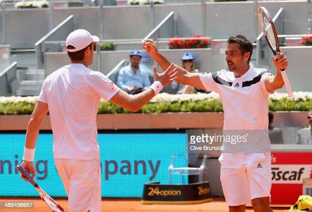 Nenad Zimonjic of Serbia and Daniel Nestor of Canada celebrate match point and their straight sets victory against Bob Bryan and Mike Bryan of the...