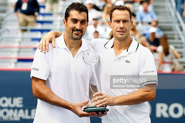 Nenad Zimonjic of Serbia and Michael Llodra of France pose for photographers after defeating the Bryan Brothers in the doubles final during the...