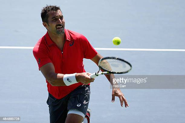 Nenad Zimonjic of Serbia returns a shot to Ivan Dodig Croatia and Marcelo Melo of Brazil during the men's doubles semifinals of the Western Southern...
