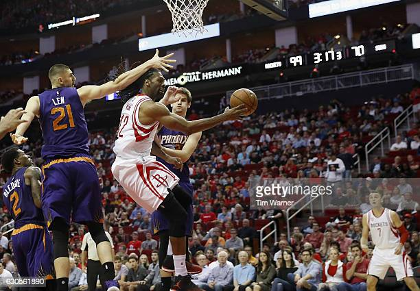 Nene Hilario of the Houston Rockets passes the ball under the basket defended by Alex Len of the Phoenix Suns and Dragan Bender of the Phoenix Suns...