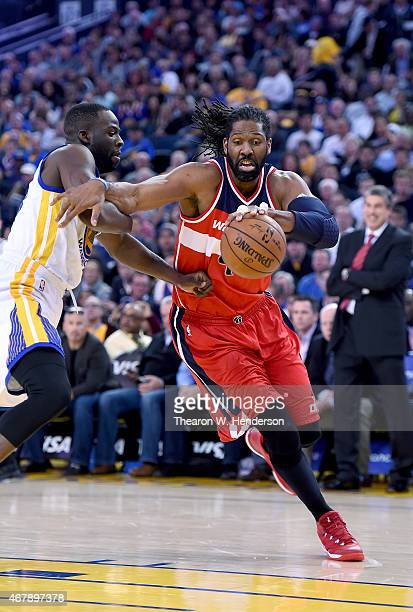 Nene Hilario of the Washington Wizards drives to the basket on Draymond Green of the Golden State Warriors at ORACLE Arena on March 23 2015 in...