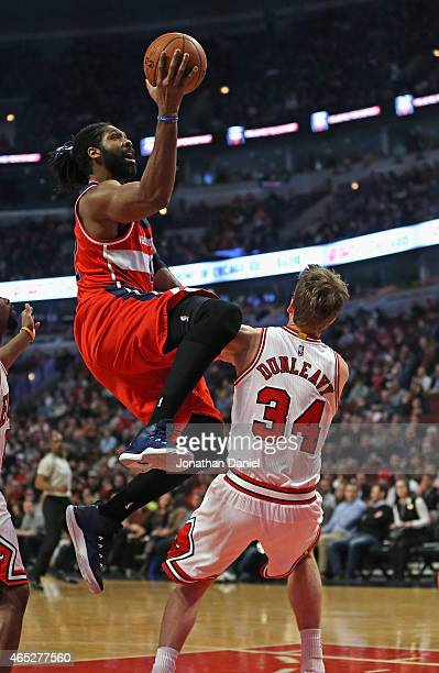Nene Hilario of the Washington Wizards goes up for a shot over Mike Dunleavy of the Chicago Bulls at the United Center on March 3 2015 in Chicago...