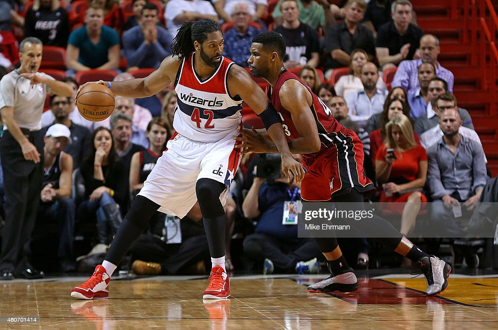 Nene Hilario #42 of the Washington Wizards posts up Shawne Williams #43 of the Miami Heat during a game at American Airlines Arena on December 19, 2014 in Miami, Florida.