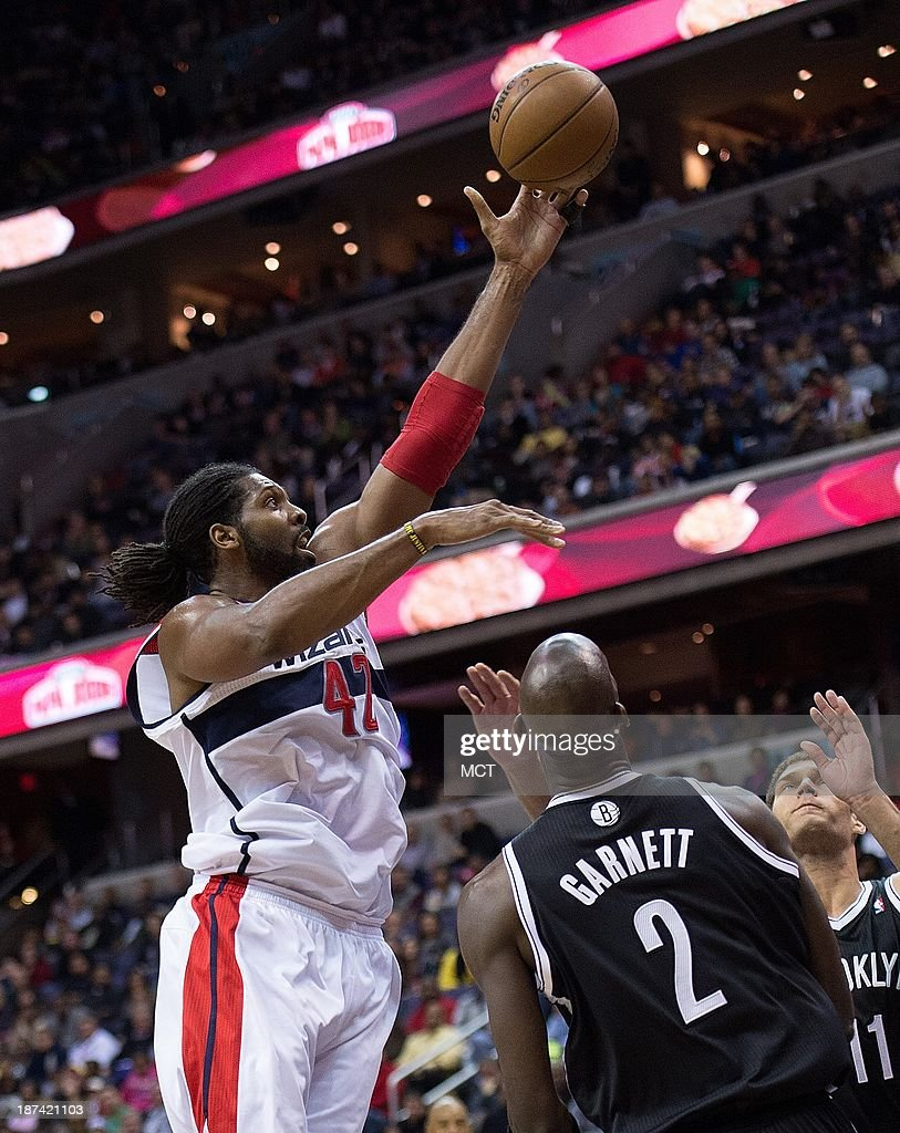 Nene Hilario (42) of the Washington Wizards shoots over Kevin Garnett (2) and Brook Lopez (11) of the Brooklyn Nets during the second half of their game played at the Verizon Center in Washington, Friday, November 8, 2013. Washington defeated Brooklyn 112-108.
