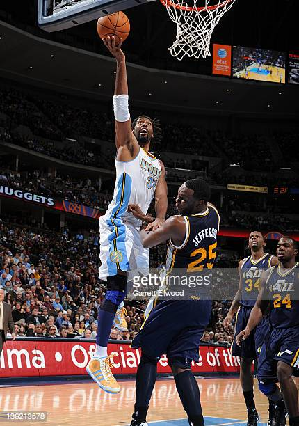 Nene of the Denver Nuggets goes to the basket against Al Jefferson of the Utah Jazz during the game on December 28 2011 at the Pepsi Center in Denver...