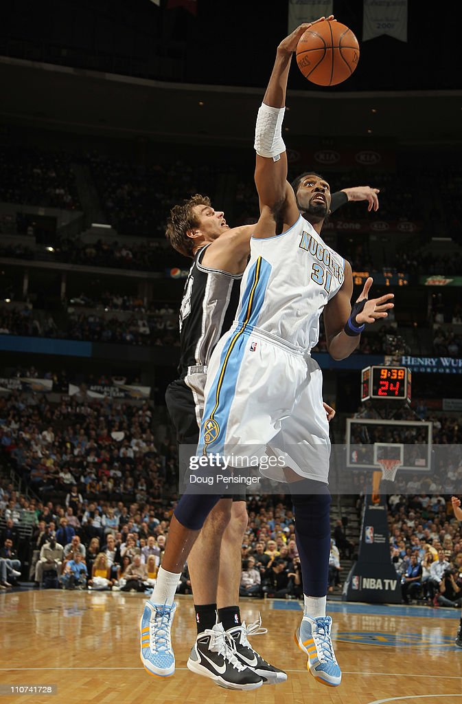 Nene #31 of the Denver Nuggets grabs a rebound away from <a gi-track='captionPersonalityLinkClicked' href=/galleries/search?phrase=Tiago+Splitter&family=editorial&specificpeople=208218 ng-click='$event.stopPropagation()'>Tiago Splitter</a> #22 at the Pepsi Center on March 23, 2011 in Denver, Colorado. The Nuggets defeated the Spurs 115-112.