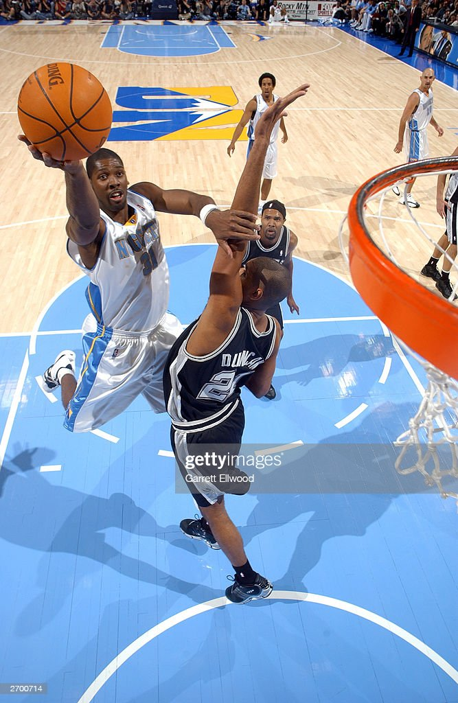 Nene #31 of the Denver Nuggets pushes away <a gi-track='captionPersonalityLinkClicked' href=/galleries/search?phrase=Tim+Duncan&family=editorial&specificpeople=201467 ng-click='$event.stopPropagation()'>Tim Duncan</a> #21 of the San Antonio Spurs during the game at the Pepsi Center on October 29, 2003 in Denver, Colorado. The Nuggets won 80-72.