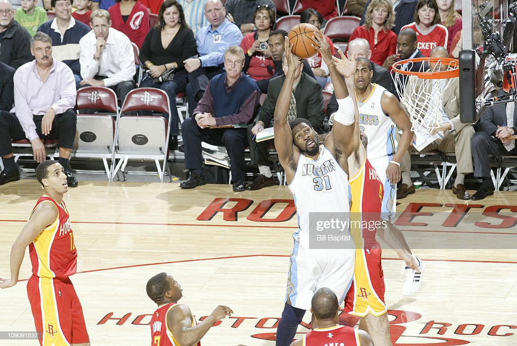 Nene #31 of the Denver Nuggets rebounds the ball over Luis Scola #4 of the Houston Rockets on February 14, 2011 at the Toyota Center in Houston, Texas.
