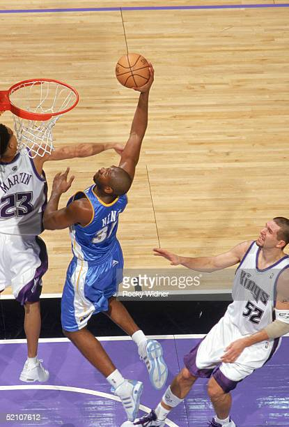 Nene of the Denver Nuggets takes the ball to the basket against Kevin Martin of the Sacramento Kings during a game at Arco Arena on January 11 2005...
