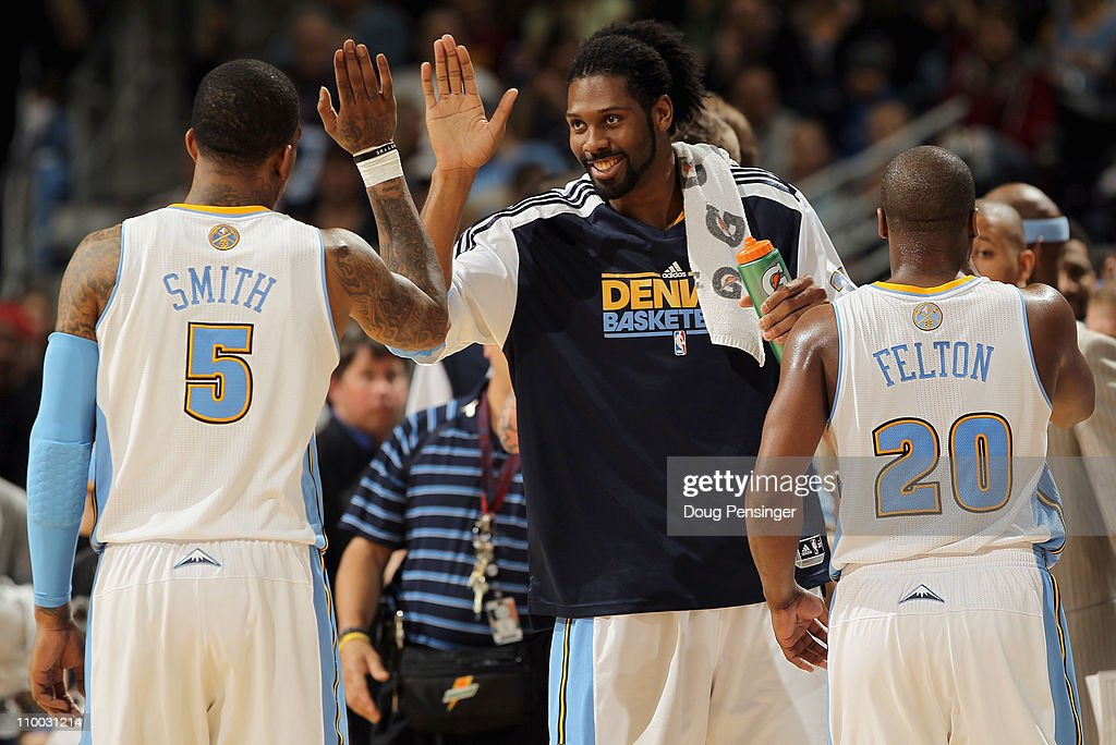 Nene #31 of the Denver Nuggets welcomes teammates J.R. Smith #5 and Raymond Felton #20 to the bench for a time out against the Detroit Pistons at the Pepsi Center on March 12, 2011 in Denver, Colorado. The Nuggets defeated the Pistons 131-101.