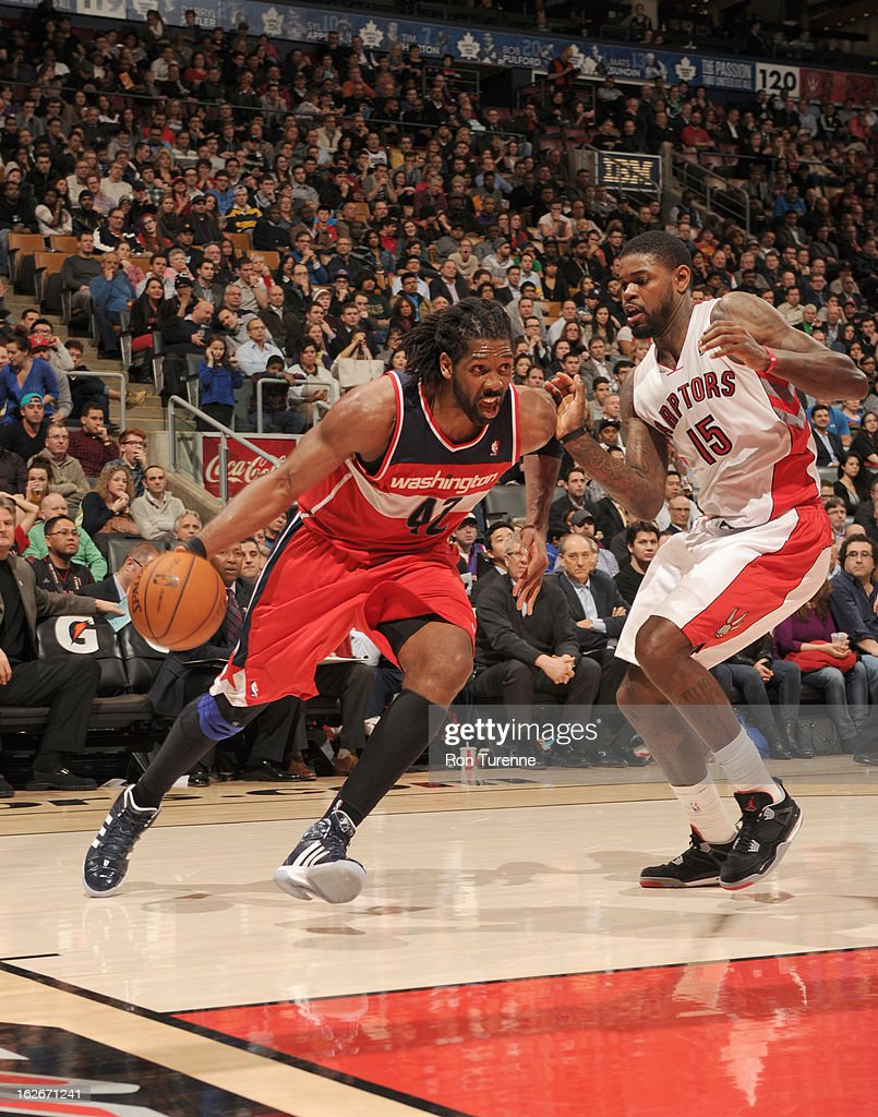 Nene #42 of the Washington Wizards drives against Amir Johnson #15 of the Toronto Raptors during the game between the Toronto Raptors and the Washington Wizards during the game on February 25, 2013 at the Air Canada Centre in Toronto, Ontario, Canada.