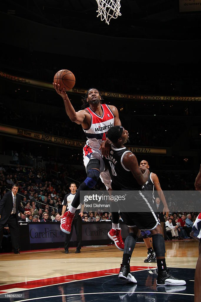 Nene #42 of the Washington Wizards drives to the basket against <a gi-track='captionPersonalityLinkClicked' href=/galleries/search?phrase=Andray+Blatche&family=editorial&specificpeople=4282797 ng-click='$event.stopPropagation()'>Andray Blatche</a> #0 of the Brooklyn Nets on January 4, 2013 at the Verizon Center in Washington, DC.