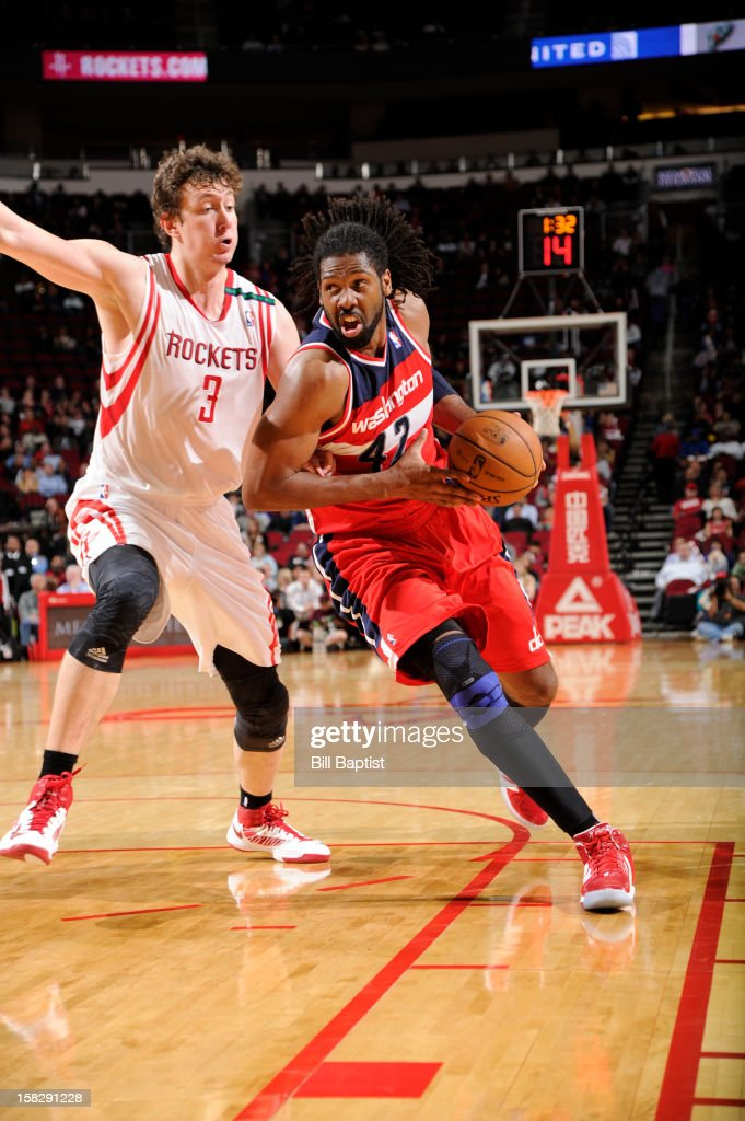 Nene #42 of the Washington Wizards drives to the basket against Omer Asik #3 of the Houston Rockets on December 12, 2012 at the Toyota Center in Houston, Texas.