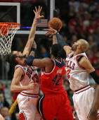 Nene of the Washington Wizards puts up a successful shot between Joakim Noah and Taj Gibson of the Chicago Bulls in Game Five of the Eastern...