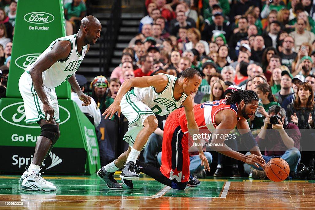 Nene #42 the Washington Wizards dives for the loose ball against Kevin Garnett #5 and Avery Bradley #0 of the Boston Celtics on April 7, 2013 at the TD Garden in Boston, Massachusetts.