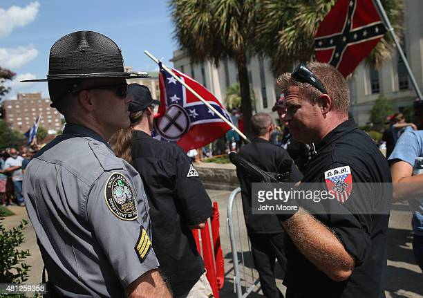 Neo Nazi member speaks with a South Carolina state policeman at a Ku Klux Klan demonstration at the state house building on July 18 2015 in Columbia...