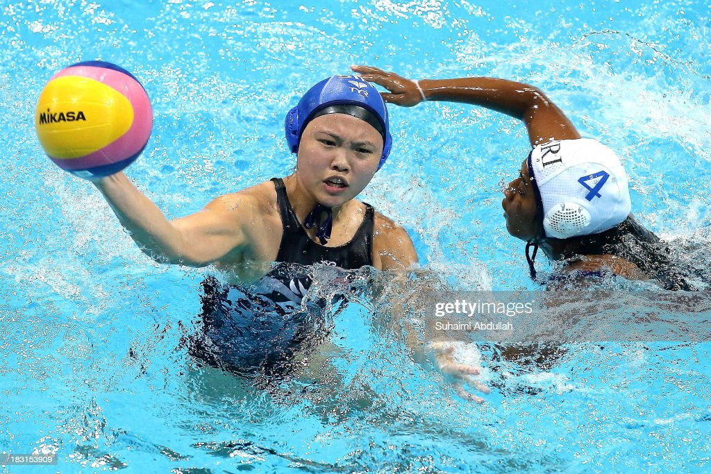 Neo Ser Han of Singapore (L) takes aim at goal under pressure from Limashi Kosgodage (R) of Sri Lanka during the women Asian Water Polo Cup between Singapore and Sri Lanka at Toa Payoh Swimming Complex on October 5, 2013 in Singapore.