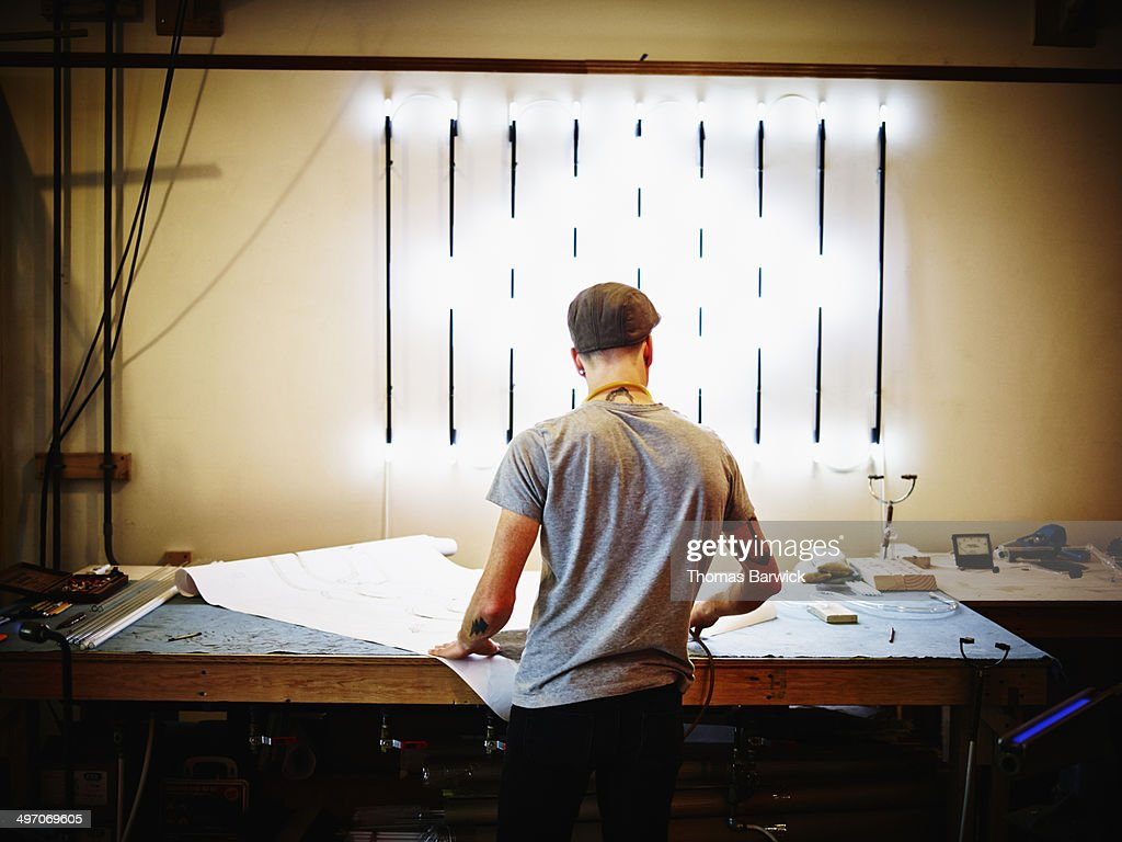 Neon artist at work table in industrial loft : Stock Photo