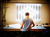Neon artist at work table in industrial loft