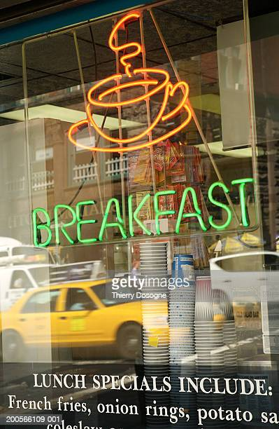 Neon 'breakfast' sign in window of cafe by busy street