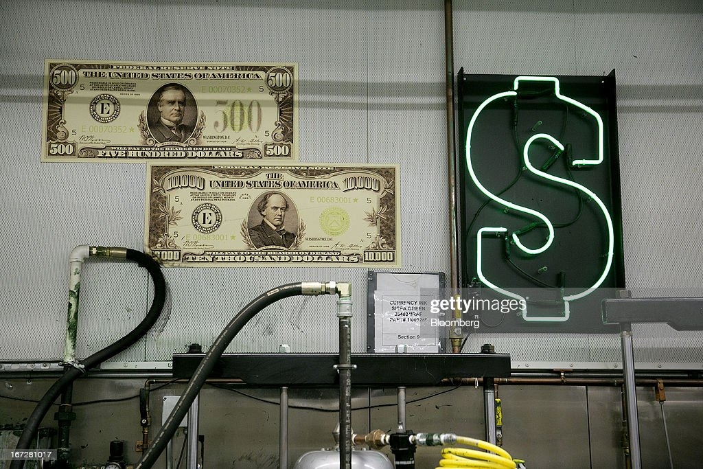 A neon dollar sign is hung on the wall at the Bureau of Engraving and Printing in Washington, D.C., U.S., on Tuesday, April 23, 2013. Stocks rallied amid growth in U.S. home sales, better-than-forecast earnings and speculation the European Central Bank will cut interest rates. U.S. equities recovered after briefly erasing gains following a false report of explosions at the White House. Photographer: Andrew Harrer/Bloomberg via Getty Images