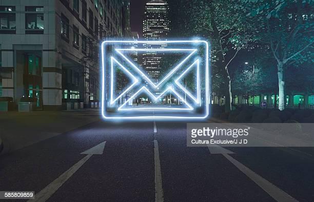 Neon envelope symbol in one way street at night
