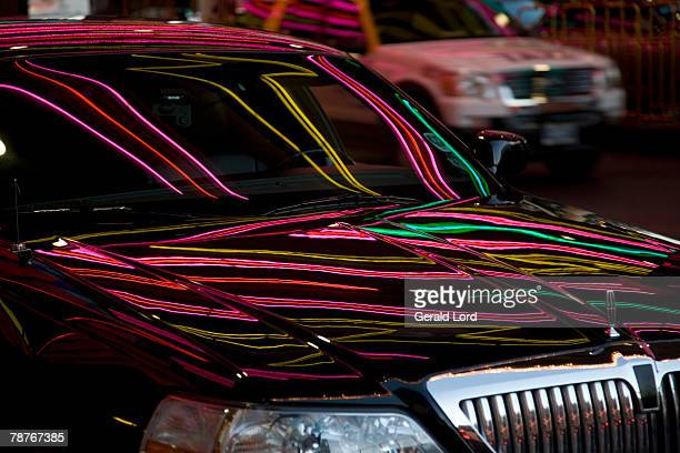 Neon lights reflecting on a limousine