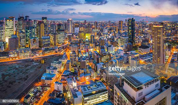 Neon night city futuristic skyscraper cityscape sunset panorama Osaka Japan
