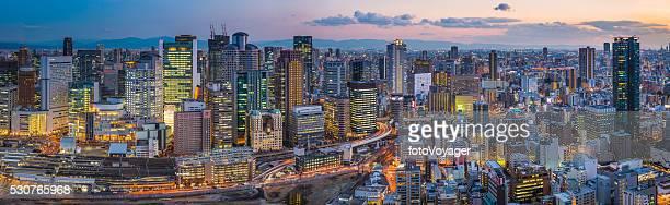 ネオンの夜の摩天楼の未来的な街のパノラマ景観照明オサカ日本