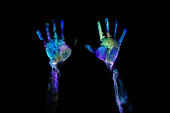 Fluorescent multicolored hand print on black background