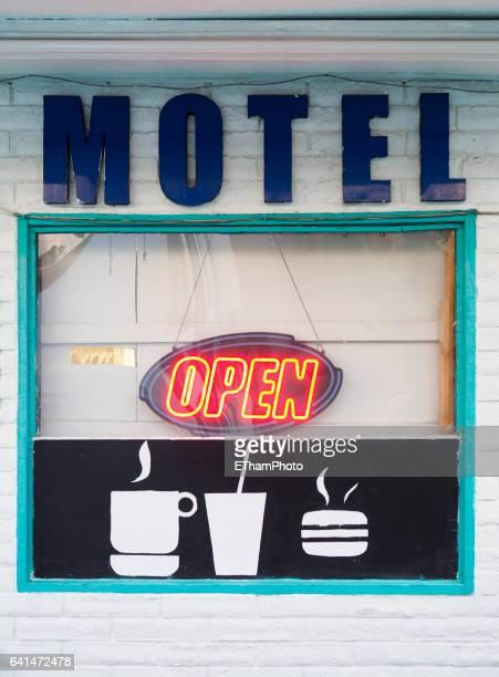 Neon sign displays 'Open' in American motel window
