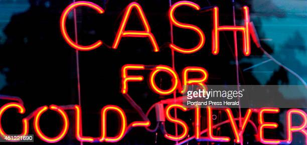 A neon sign in a pawn shop window offers cash to customers for gold and silver Mainers use payday loans pawn shop loans renttoown agreements and...