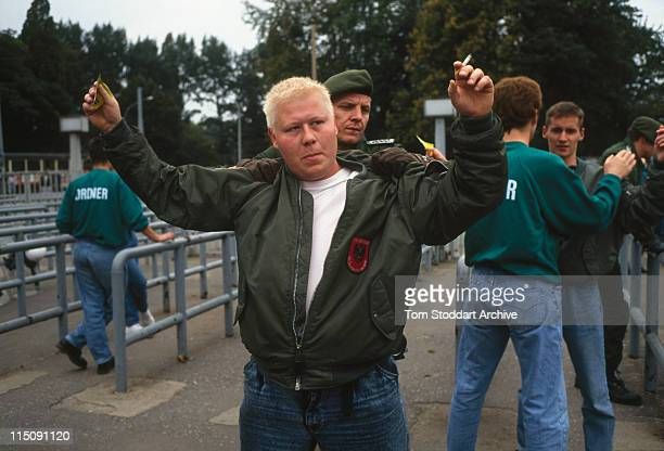 A neoNazi follower being searched by German police outside a football ground in Bremen After German reunification in the early 1990's neoNazi groups...