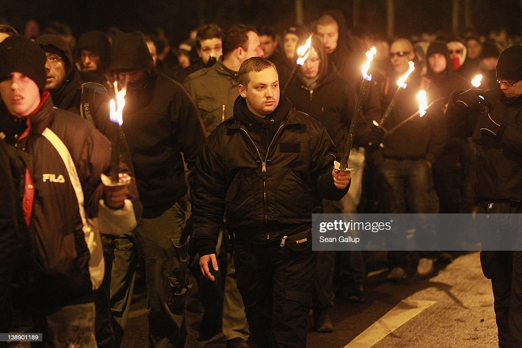 Neo-Nazis and their sympathizers march with torches to commemorate the World War II firebombing of Dresden by Allied planes on February 13, 2012 in Dresden, Germany. Protesters attempted unsuccessfully to surround the expected 1,500 neo-Nazis with a human chain in order to prevent them from marching through the city in the annual event. Right-wing extremism is currently making national headlines in Germany due to the revelation that a pair of neo-Nazis claiming to be part of a group called the National Socialist Underground (NSU) murdered at least 10 immigrant small-business owners as well as a policewoman over a decade-long period, and that police investigations at the time were either botched or willfully aborted.