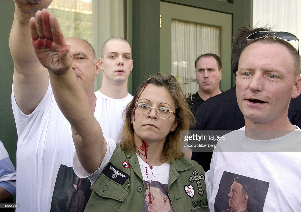 NeoNazis stop to salute as they are chased by protesters outside the Wakefield Town of Beebe Public Library September 14 2002 in Wakefield...