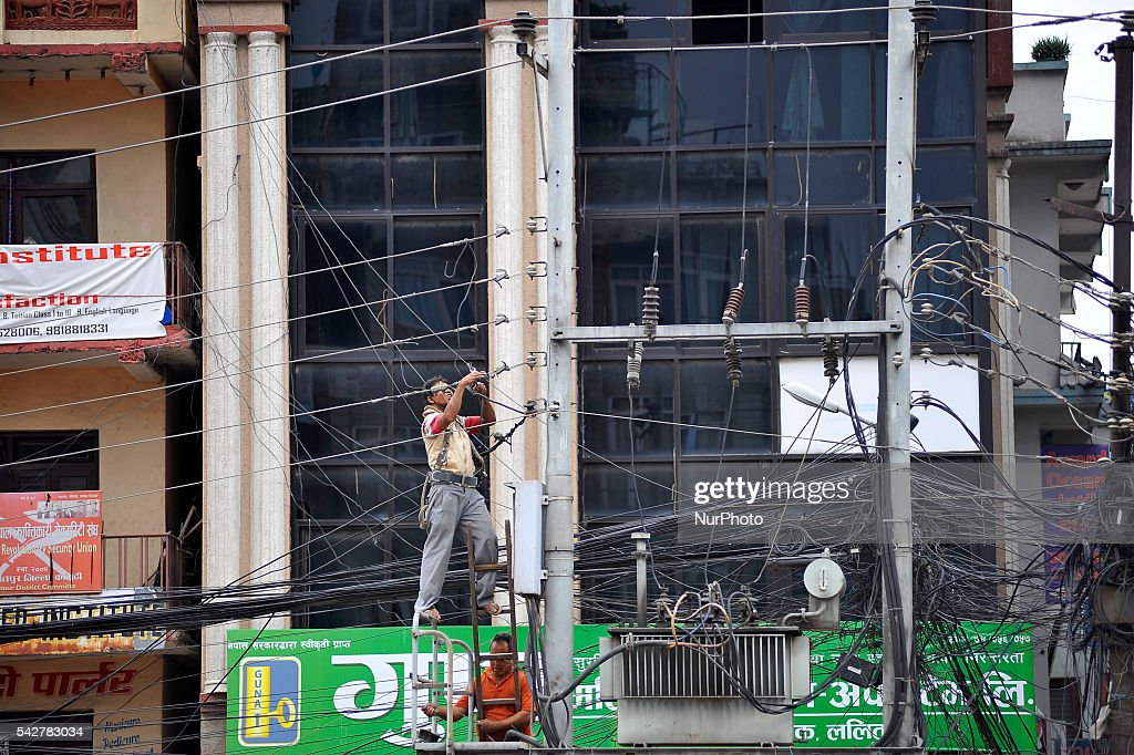 Nepal Electricity Authority (NEA) Staff Worker arranging very messy Electricity wire due to the destruction of Electric Pole at Pulchowk, Patan, Nepal on June 24, 2016.