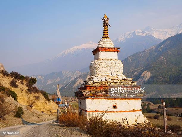 Nepal, Manang, Munchi: Large chorten beside road in valley in Annapurna Himalayas